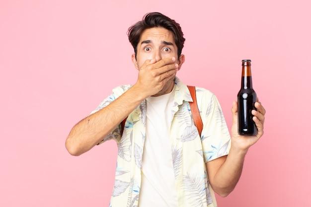 Giovane ispanico che copre la bocca con le mani con uno shock e tiene in mano una bottiglia di birra