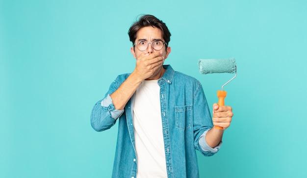 Giovane ispanico che copre la bocca con le mani con uno shock e tiene in mano un rullo di vernice