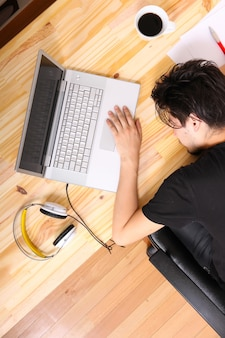 Un giovane uomo ispanico addormentarsi alla scrivania in ufficio.