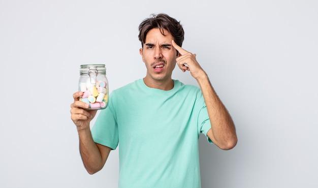 Giovane ispanico che si sente confuso e perplesso, mostrando che sei pazzo. concetto di caramelle di gelatina
