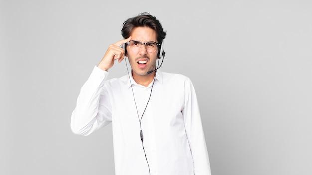 Giovane ispanico che si sente confuso e perplesso, mostrando che sei pazzo. concetto di telemarketing