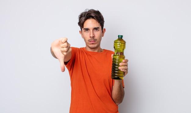 Giovane ispanico che si sente croce, mostra il pollice verso il basso. concetto di olio d'oliva