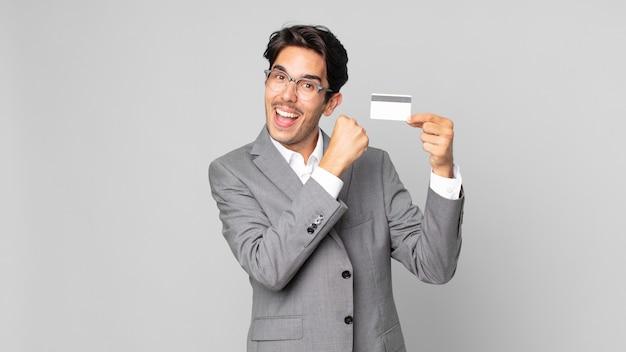 Giovane ispanico che si sente felice e affronta una sfida o festeggia e tiene in mano una carta di credito