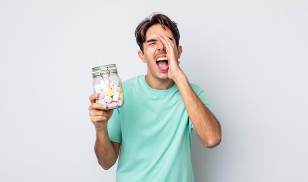 Giovane ispanico sentirsi felice, dando un grande grido con le mani vicino alla bocca. concetto di caramelle di gelatina