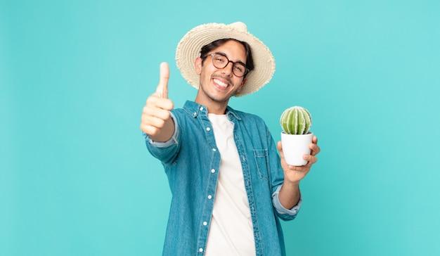 Giovane ispanico che si sente orgoglioso, sorride positivamente con il pollice in alto e tiene in mano un cactus