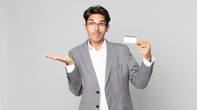 Giovane uomo ispanico che si sente perplesso e confuso e dubita e tiene in mano una carta di credito