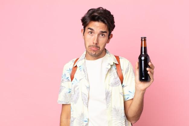Giovane ispanico che si sente triste e piagnucoloso con uno sguardo infelice e piange e tiene in mano una bottiglia di birra