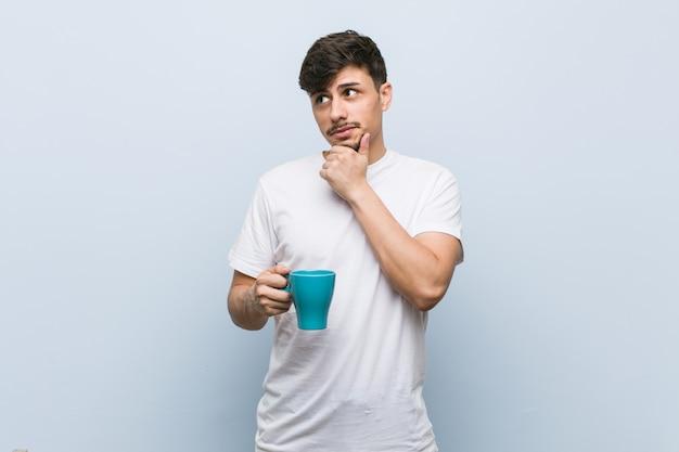 Giovane uomo ispanico che tiene una tazza che guarda lateralmente con espressione dubbiosa e scettica.