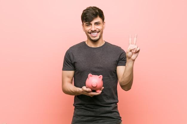 Giovane uomo ispanico che tiene banca piggy che mostra il numero due con le dita.
