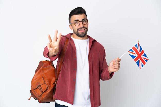 Giovane uomo ispanico che tiene una bandiera del regno unito felice e che conta tre con le dita