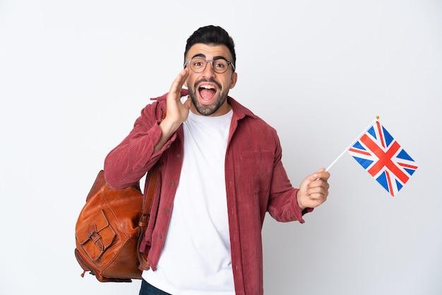 Giovane uomo ispanico che tiene una bandiera del regno unito che grida con la bocca spalancata