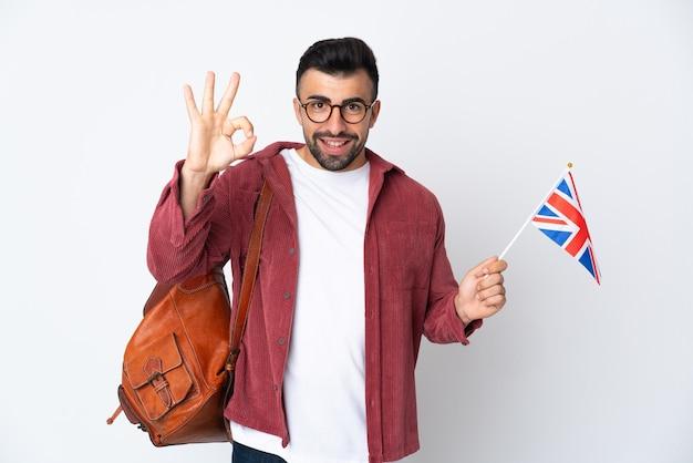 Giovane uomo ispanico che tiene una bandiera del regno unito che mostra segno giusto con le dita