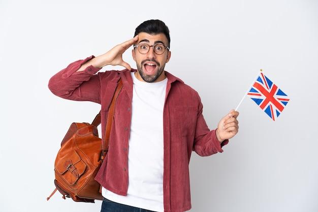 Giovane uomo ispanico che tiene una bandiera del regno unito con espressione di sorpresa