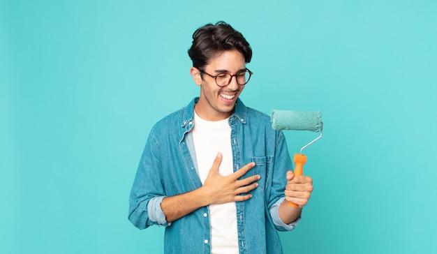 Giovane ispanico che ride ad alta voce per uno scherzo esilarante e tiene in mano un rullo di vernice