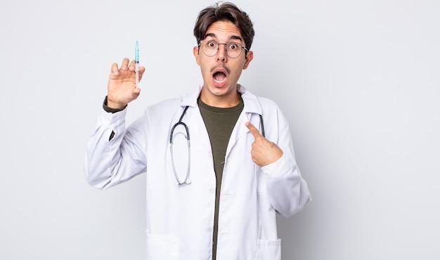 Giovane uomo ispanico che sembra scioccato e sorpreso con la bocca spalancata, che indica se stesso. concetto di siringa medico
