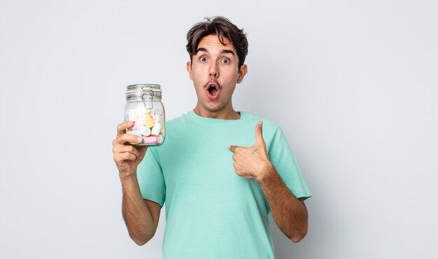 Giovane uomo ispanico che sembra scioccato e sorpreso con la bocca spalancata, che indica se stesso. concetto di caramelle di gelatina
