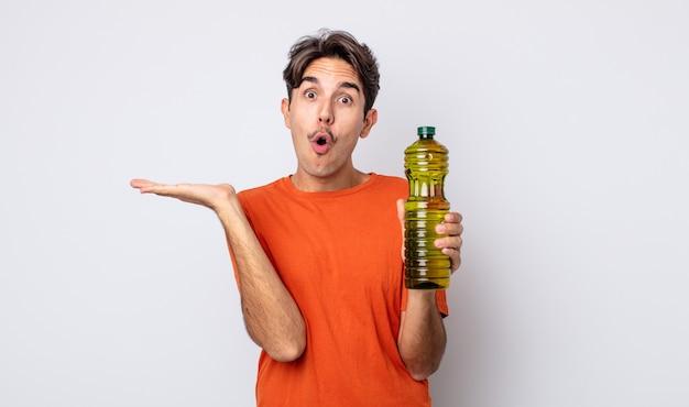 Giovane uomo ispanico che sembra sorpreso e scioccato, con la mascella caduta in possesso di un oggetto. concetto di olio d'oliva