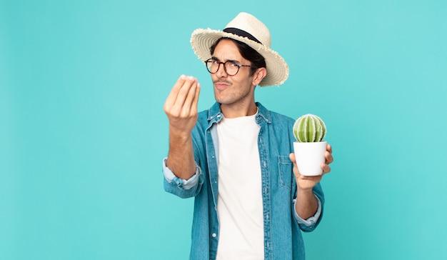 Giovane ispanico che fa un gesto di denaro o di denaro, dicendoti di pagare e tenendo in mano un cactus