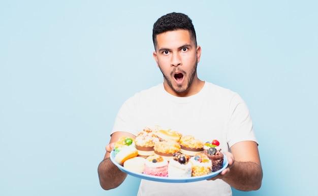 Giovane uomo ispanico espressione spaventata che tiene cupcakes