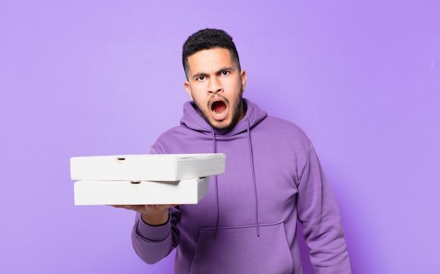 Il giovane ispanico ha paura dell'espressione e tiene le pizze da asporto