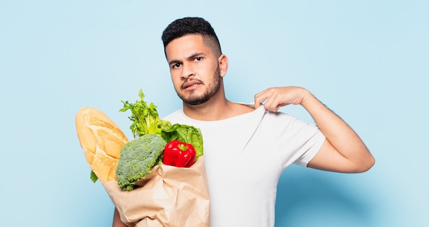 Espressione spaventata del giovane uomo ispanico. concetto di acquisto di verdure
