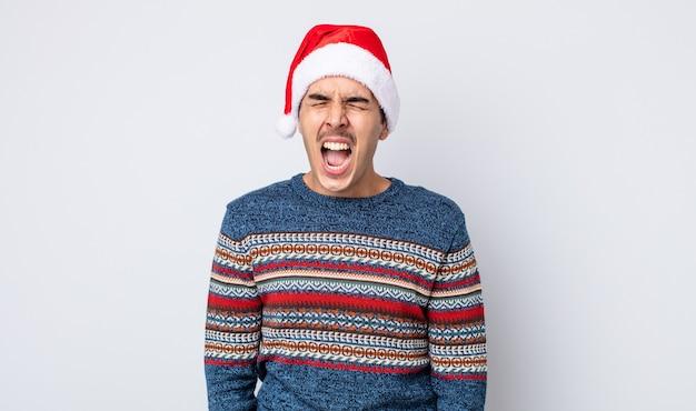 Giovane ispanico che grida in modo aggressivo, sembra molto arrabbiato. concetto di capodanno e natale