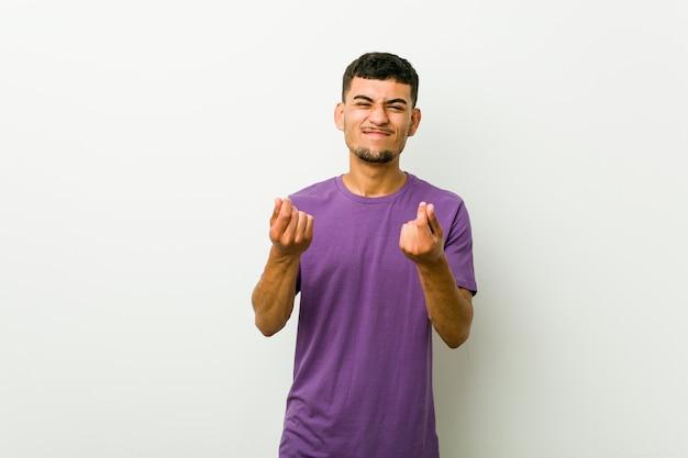 Giovane uomo ispanico che mostra di non avere soldi.