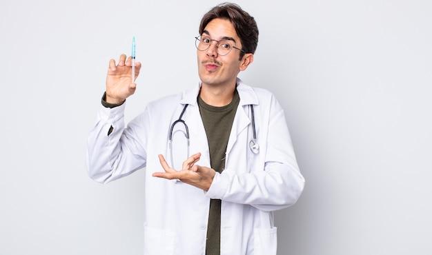 Giovane ispanico che alza le spalle, sentendosi confuso e incerto. concetto di siringa medico