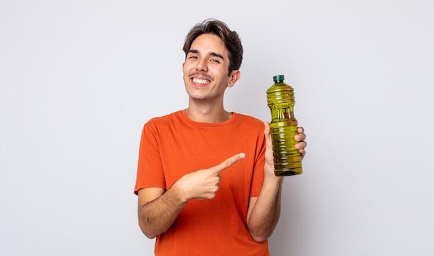 Giovane ispanico che sorride allegramente, si sente felice e indica il lato. concetto di olio d'oliva