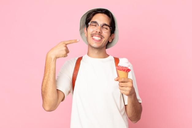 Giovane uomo ispanico che sorride con sicurezza indicando il proprio ampio sorriso e tenendo in mano un gelato