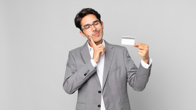 Giovane ispanico che sorride felice e sogna ad occhi aperti o dubita e tiene in mano una carta di credito