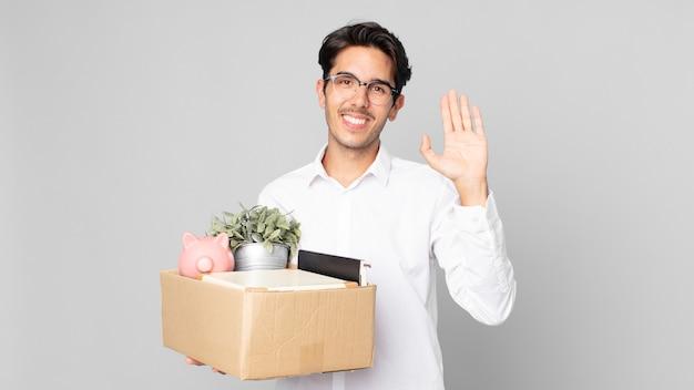 Giovane uomo ispanico che sorride felicemente, agitando la mano, accogliendoti e salutandoti. concetto di licenziamento