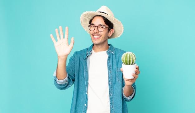 Giovane ispanico che sorride felicemente, agitando la mano, accogliendoti e salutandoti e tenendo in mano un cactus