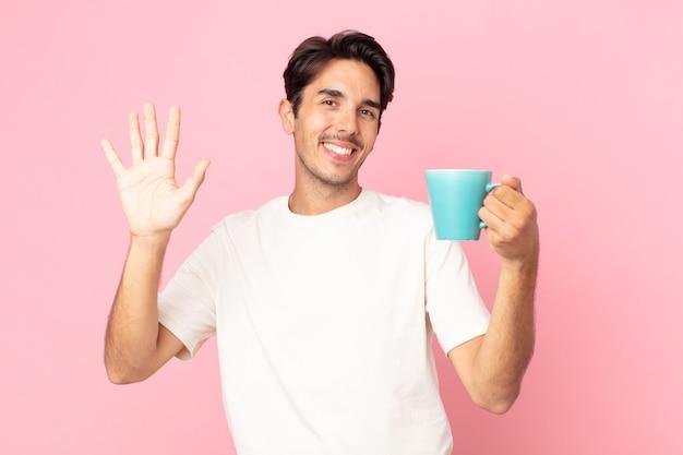 Giovane ispanico che sorride felicemente, agitando la mano, accogliendoti e salutandoti e tenendo in mano una tazza di caffè