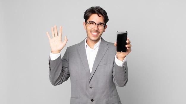 Giovane ispanico che sorride felicemente, agitando la mano, accogliendoti e salutandoti e tenendo in mano uno smartphone