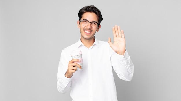 Giovane ispanico che sorride felicemente, agitando la mano, accogliendoti e salutandoti e tenendo in mano un caffè da asporto