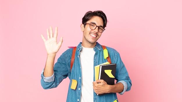 Giovane uomo ispanico che sorride felicemente, agitando la mano, accogliendoti e salutandoti. concetto di studente