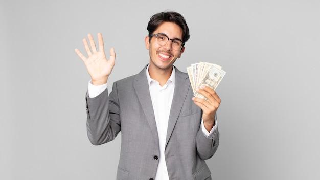 Giovane uomo ispanico che sorride felicemente, agitando la mano, accogliendoti e salutandoti