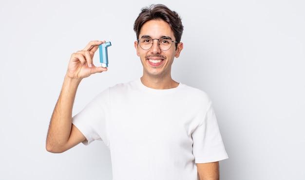 Giovane ispanico che sorride felicemente con una mano sull'anca e fiducioso. concetto di asma