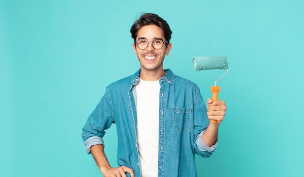 Giovane uomo ispanico che sorride felicemente con una mano sull'anca e fiducioso e tiene in mano un rullo di vernice