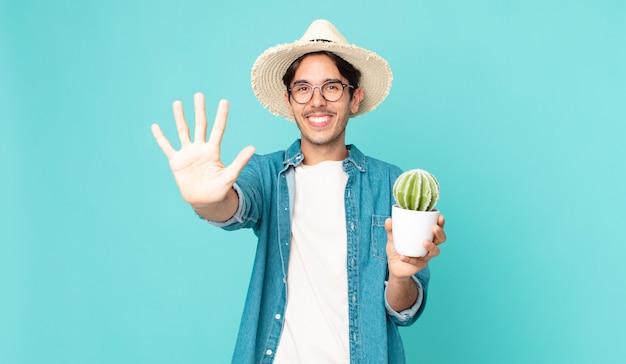 Giovane ispanico che sorride e sembra amichevole, mostra il numero cinque e tiene in mano un cactus