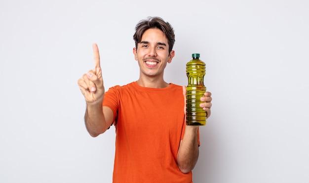 Giovane ispanico sorridente e dall'aspetto amichevole, mostrando il numero uno. concetto di olio d'oliva