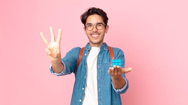 Giovane ispanico che sorride e sembra amichevole, mostrando il numero tre con un gioco di sfida dell'intelligenza