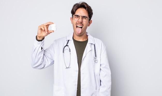 Giovane ispanico con atteggiamento allegro e ribelle, scherzando e tirando fuori la lingua. medico con il concetto di bottiglia di pillole
