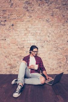 Giovane uomo ispanico con una tazza di caffè che digita sul computer portatile