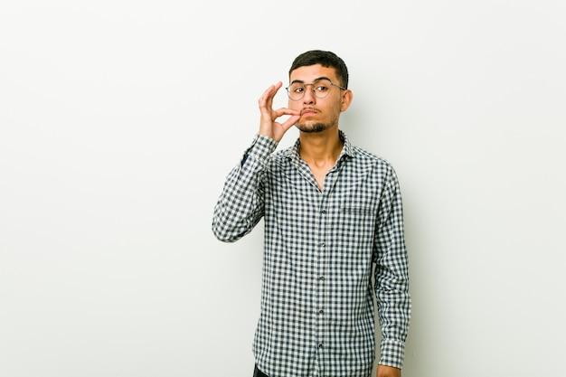 Giovane uomo ispanico con le dita sulle labbra mantenendo un segreto.