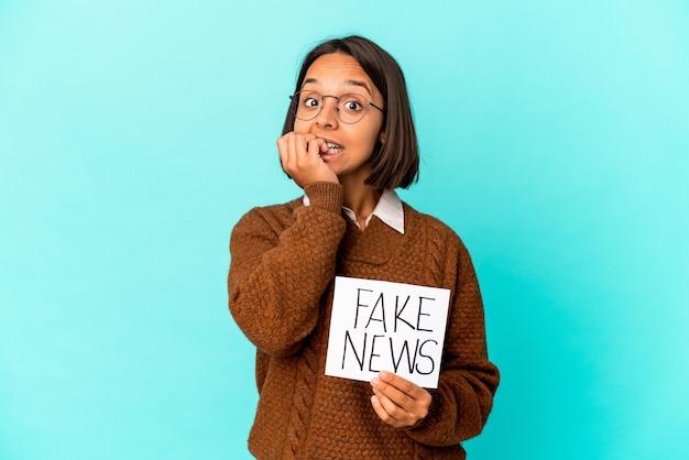 Giovane donna ispanica di razza mista che tiene un cartello di notizie false che si morde le unghie, nervosa e molto ansiosa.
