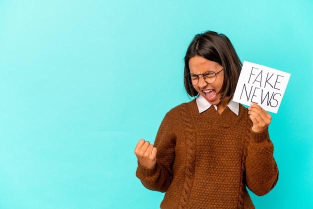 Giovane donna ispanica della corsa mista che tiene un cartello di notizie false che alza il pugno dopo una vittoria, concetto del vincitore. Foto Premium
