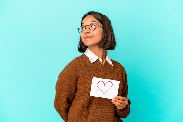 Giovane donna ispanica di razza mista che tiene una carta del cuore che sogna di raggiungere obiettivi e scopi