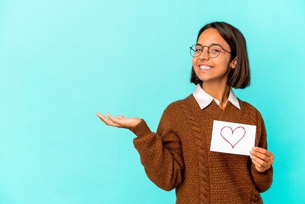 Giovane donna ispanica di razza mista che tiene un foglio di cuore che mostra uno spazio di copia su un palmo e che tiene un'altra mano sulla vita.